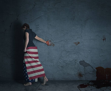 young woman at a grey wall wearing american flag with a blood trail behind her photo