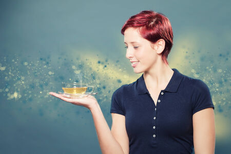 redhead woman holding a cup of yellow tea photo