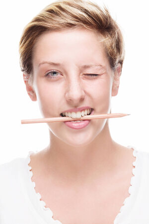 blonde happy woman winking with pencil in her mouth on white background photo