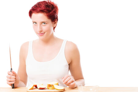 diabolic looking woman with a knife and a sliced apple on white background photo