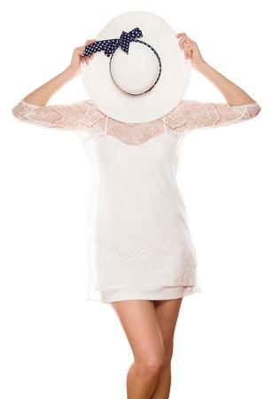 jonge vrouw in witte kleding verbergt haar gezicht achter hoed zon op een witte achtergrond Stockfoto