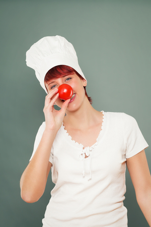 young female cook holding tomato on her nose photo
