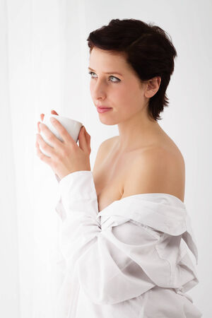 button down shirt: sensual woman at a window holding coffee wearing a white button down shirt Stock Photo