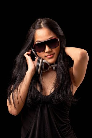A young asian girl in a black dress and sunglassses listening to music from dj style headphones. Stock Photo