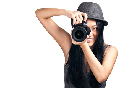 A pretty asian girl taking photos with a DSLR and smiling.