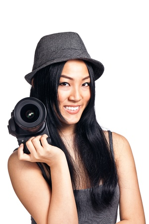A young asian girl posing and smiling with a DSLR camera. Stock Photo
