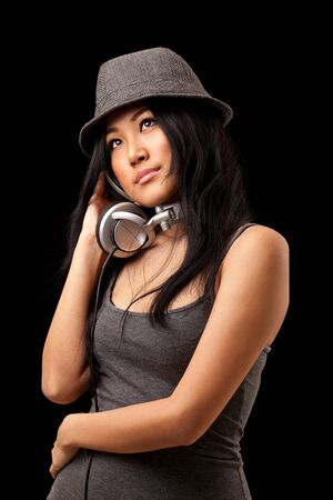 A young asian girl dressed in stylish clothes listening to music from dj style headphones. photo