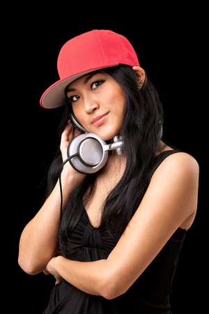 A young asian girl in a black dress and red hat listening to music from dj style headphones. Stock Photo