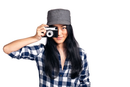 A young asian girl having fun with a camera over one eye while getting ready to take a photo. Standard-Bild