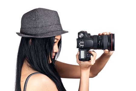 A young asian girl looking through the viewfinder of an DSLR and getting ready to take a photo.