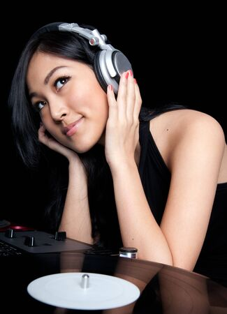 An Asian girl listening to music in front of a pair of turntables and mixer.