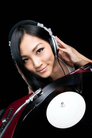 A young female listening to music in front of a pair of turntables and mixer. photo