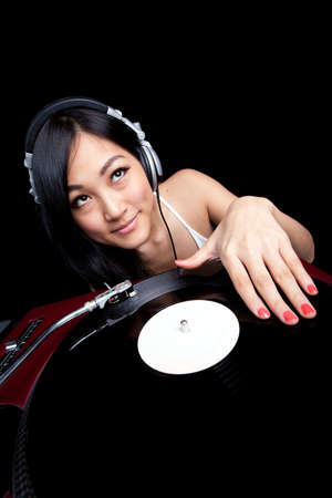 deejay: An Asian girl DJing on red turntable isolated on black.