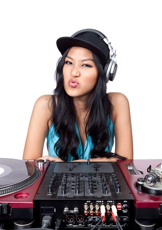 A young Asian female DJ making a funny face in front of a mixer and pair of turntables. photo