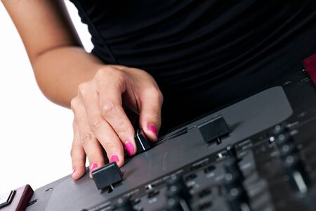 crossfader: A female hand with pink nails using the crossfader of a mixer