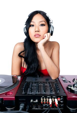 A young female Asian DJ listening to music in front of her gear. photo
