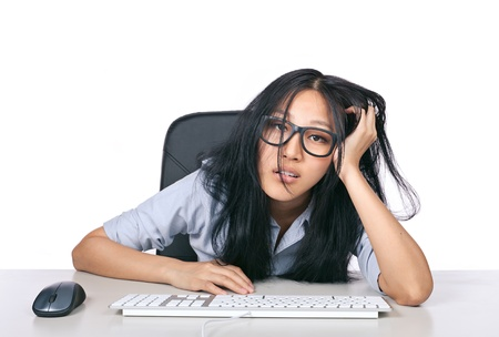 A young girl with glasses looking stressed out sitting a desk with a keyboard and mouse Standard-Bild