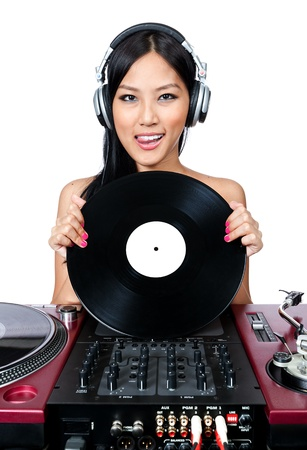 A young female Asian DJ holding a record while standing in front of a mixer and turntables