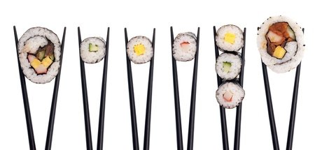 Five pieves of sushi in a row being held up with black chopsticks isolated on a white background.