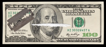 methamphetamine: A 100 dollar bill with a line of white powder and razor on it.