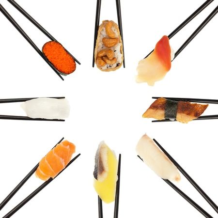 8 different types of sushi being held up in in a circle formation with black chopsticks isolated on white. photo
