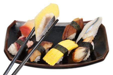 A small platter of sushi with chopsticks grabbing a piece of saba kazunoko (mackerel and roe) photo