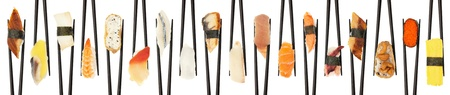 18 different types of sushi being held up in in a criss-cross line with black chopsticks isolated on white. Standard-Bild
