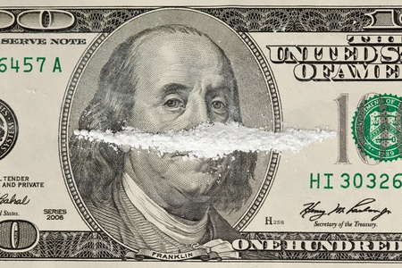 A 100 dollar bill with a line of white powder and on it.