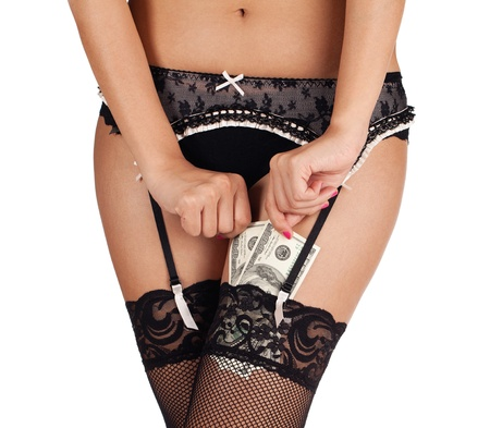 A woman in lace stockings and underwear putting money in her stockings. Stock Photo