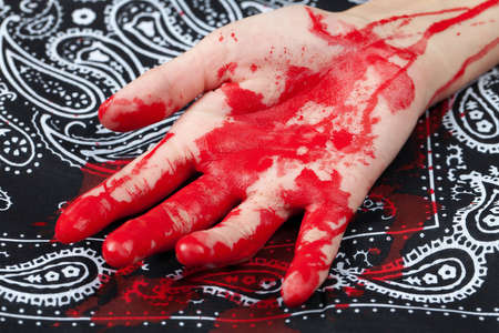 bloodstains: A bloody hand on top of a black bandana.