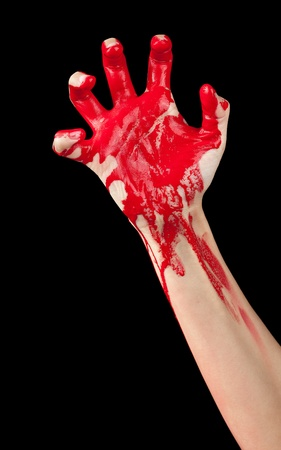 bloodstains: A red paint covered hand clenching isolated on black.