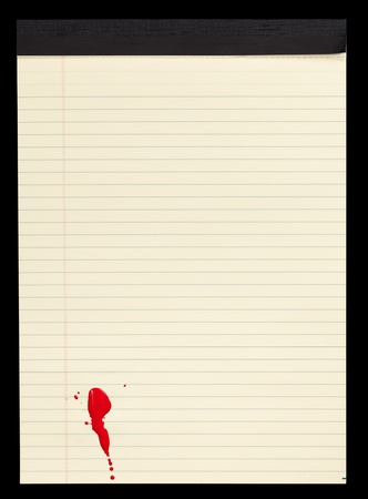 A sheet of lined yellow notepad paper with red blood stains (paint) on it. photo