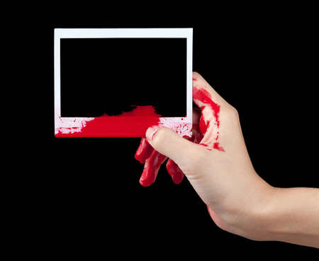 A blood covered hand holding up a piece of blank instant film isolated on black. Stock Photo - 12805408