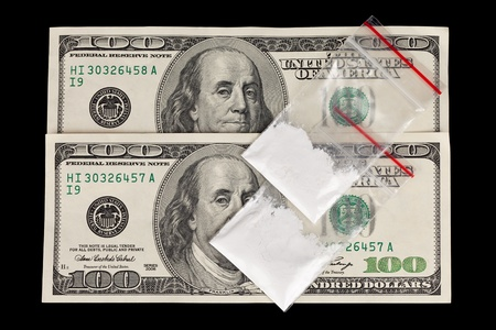 smuggling: Two 100 dollar bills with 2 bags of white powder on them.