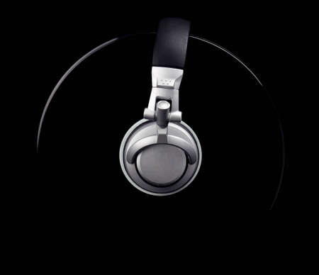 shiny metal background: A pair of DJ style headphones wrapped around a record isolated on black. Stock Photo