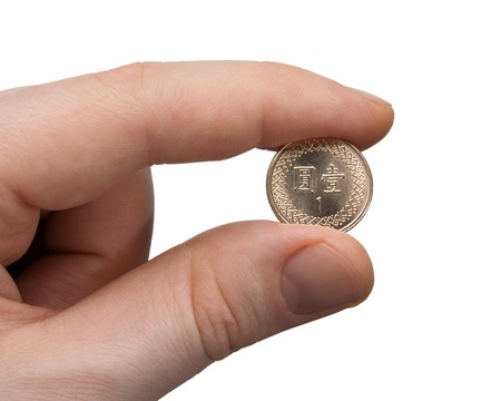 A male thumb and index finger gripping a New Taiwan 1 Dollar Coin