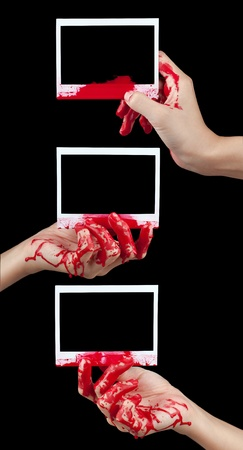 bloodstains: A composite of 3 blood covered hands holding up pieces of blank instant film isolated on black
