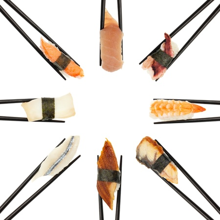 8 different types of sushi being held up in in a circle formation with black chopsticks isolated on white  photo