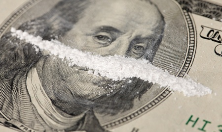 methamphetamine: A close-up of a 100 dollar bill with a line of white powder and on it