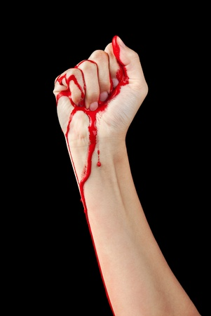 clenching fists: A red paint soaked hand making a fist isolated on black