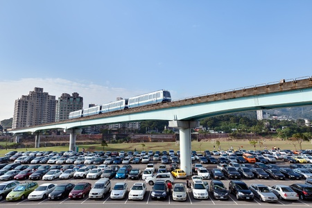 A shot of a Taipei MRT train crossing over a busy parking lot on the outskirts of the city between Muzha and Taipei Zoo Station