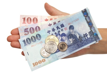 A hand holding the most commonly used coins and notes in Taiwan.