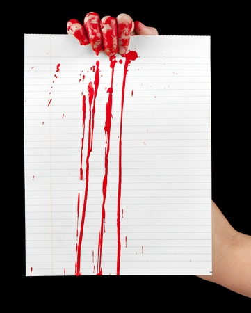 bloodstains: A blood covered hand holding up a piece of blood covered lined paper isolated on black.