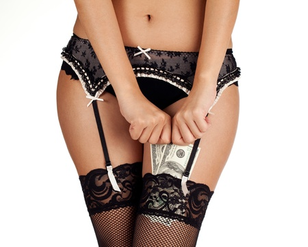 A woman in lace stockings and underwear putting money in her stockings. photo