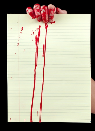 bloodstains: A blood covered hand holding up a piece of blood covered yellow lined paper isolated on black.