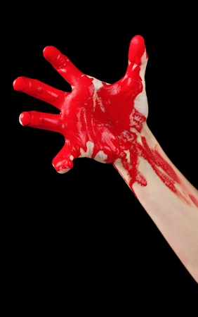 A red paint covered hand reaching out isolated on black  photo