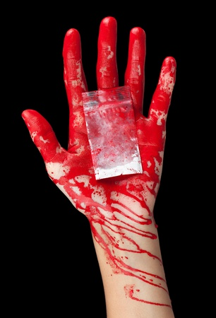A blood covered hand holding out a bag of white powder isolated on black  photo