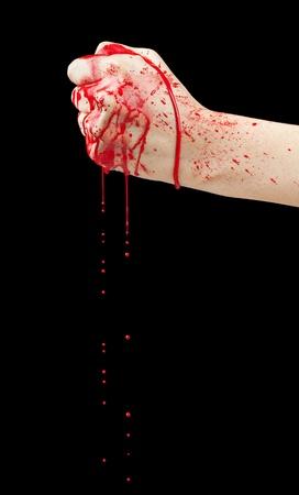 A bloody hand making a fist with blood dripping down isolated on black