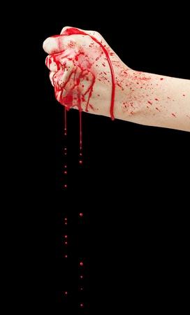 pu�os: Una mano ensangrentada haciendo un pu�o con la sangre goteando aisladas en negro Foto de archivo