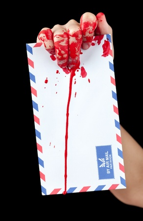 A blood covered hand holding up a blood covered air mail enveolped isolated on black  Stock Photo - 13418350